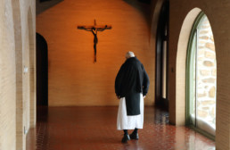 Monk gazing at crucifix in cloister walkway