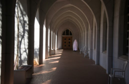 monk in white cowl in distance walking down sunlight cloister arcade