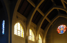 sunlight shining through stainglass windows in church upper level
