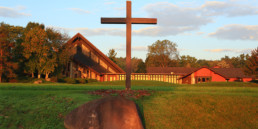 front exterior of Genesee Abbey church, with wooden cross in front