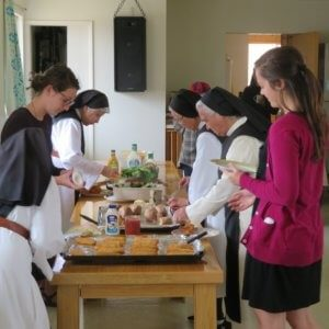 nuns and retreatants in serving line with plates