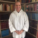 Smiling man in white postulant's smock standing in front of bookcase.