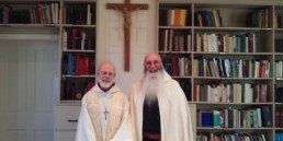 Br. John and Abbot smiling in front of crucifix and bookcase