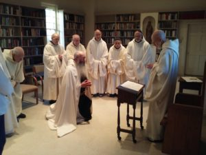Br. John kneeling before monastic community
