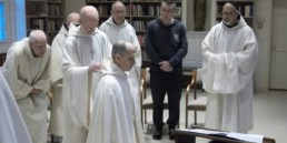 Br. Elijah new novice dressed in white smock prostrate before abbot and monastic community