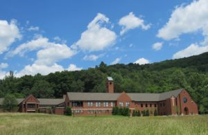 Our Lady of the Angels monastey. Large brick building in green field and hills under blue cloud filled sky