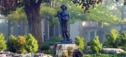 stature of Blessed Mother offering infant Jesus placed in wooded garden in front of a house