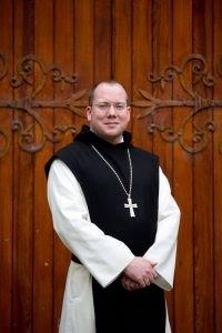 Trappist abbot standing in front of wooden door of Church