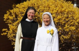 Sr. Sharon and Mother Vicky smiling in front of yellow bush