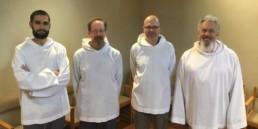 Four smiling men in white smocks