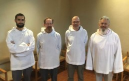 Four smiling men in white smocks