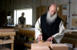 Monks working with wood blocks in carpenter shop