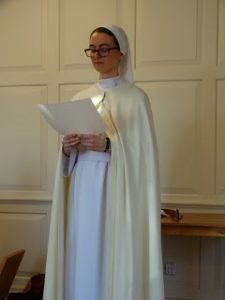 Nun in white habit standing and reading from document