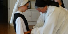 a nun kneeling and being clothed in belt of new habit by Mother Superior