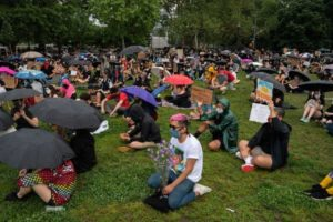 protesters wearing masks and sitting in green lawn