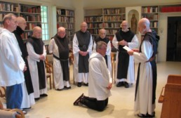 Br. Paul enters Holy Cross Abbey as a Postulant, kneeling surrounded by fellow monks