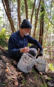 Fr. Casey at Redwoods Abbey, with buckets on side of forest slope