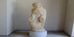 White stone sculpture of the Blessed Virgin Mary wearing cloak with hands held out by Dom Hubert Van Zellar