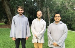 Three smiling men in grey smocks