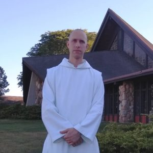 Br. Placid, monk in white habit standing in front of Genesee Abbey Church