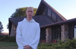 Br. Placid, monk in white habit, standing in front of Genesee Abbey Church