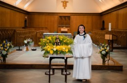 Sr Karla in new cowl smiles in front of the altar