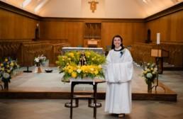 Sr Karla in new cowl smiles in front of the altar
