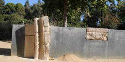 blocks of ancient stone inlayed into concrete wall