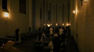 monks in darkened church, lit by candles