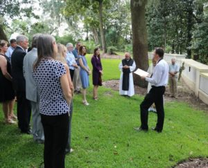 group stands on grass listening to service at Mepkin Columbarium wall