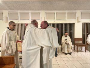Fr. Paul Mark receives congratulary hug from fellow monk in cowl