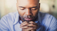 man in prayer with eyes closed and hands folded