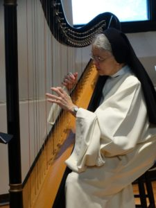 Sister Kathleen playing the harp in habit