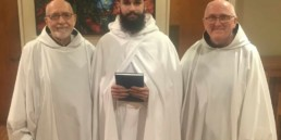 Br. Matthew enters novitiate, smiling holding book between abbot and Novice Director