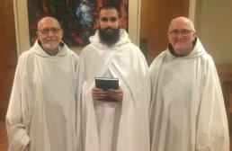 Br. Matthew enters novitiate: Matthew in novice cloak and habit, standing between abbot Fr. Joe and Novice Director, Fr. Kevin
