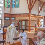 Br. Scott kneels before abbot, clothed in new cowl